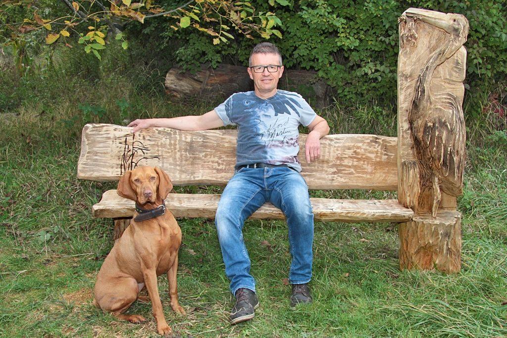 Bernd Messemer sitzt auf einer selbst gefertigten Holzbank aus massivem Eichenholz